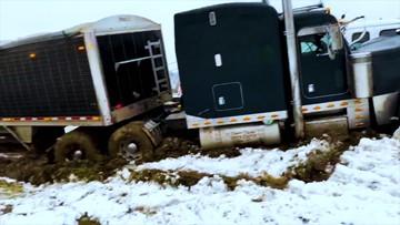Truck slides off slick highway