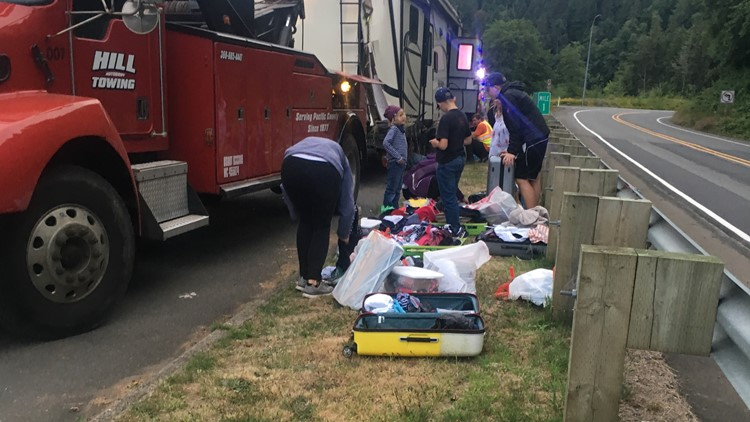 The Fischers and emergency responders collect their items that were dispersed after their truck and trailer fell into the ditch on State Route 401.