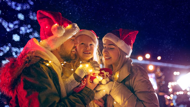 family, christmas, holidays, christmas season and people concept - happy family over lights city background and snow at night festival christmas decorations