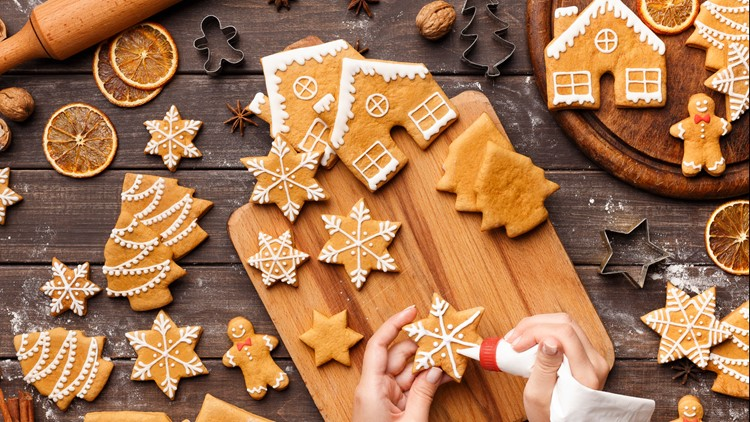 Icing process of Christmas baker decorating homemade gingerbread cookies on wooden table