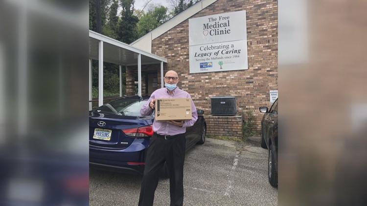 Freddie Strange, Jr., holds box of N-95 mask donations